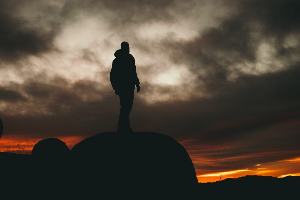 man standing on rock during golden hour